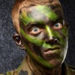 Closeup of angry soldier with painting — Stock Photo