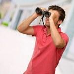 Casual man looking into binocular — Stock Photo #19518245