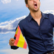 Man cheering and holding flag - Stock Photo