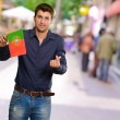 Young Man Holding Portugal Flag Gesturing - Stock Photo