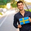 Young Happy Man Holding Sweden Flag — Stock Photo #19519089