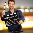 Happy Young Man Holding Clapboard - Stock Photo