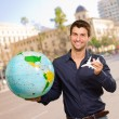 Young Man Holding Globe And Miniature - Stock Photo
