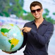 Young Man Wearing Goggle Showing Destination — Stock Photo #19519691