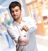 A Businessman Putting A Coin Into A Pink Piggy Bank — Stock Photo