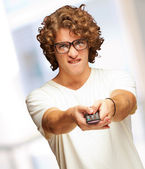 Portrait Of Young Man With Glasses Changing Channel With Tv Cont — Stock Photo