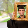 Graduate man looking through a frame — Stock Photo #19520227