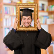 Stock Photo: Graduate mlooking through frame