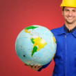 Happy Young Construction Worker Holding Globe And Brick - Stock Photo