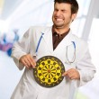 Stock Photo: Scared Young Doctor Holding Bulls Eye