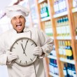 Male Chef Holding Wall Clock - Stock Photo
