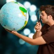 Man Looking Through Magnifying Glass At Globe — Stock Photo