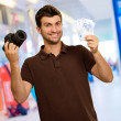 Young Man Holding Camera And Euro Currency - Stock Photo