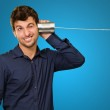 Young Man Listening From Tin Can Telephone — Stock Photo #19525193