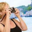 Mature Woman Holding Camera - Stock Photo