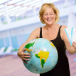 Mature Woman Holding Globe And Boarding Pass — Stock Photo
