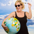 Mature Woman Holding Globe And Miniature Airplane — Stock Photo