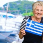 Happy Senior Woman Holding Greece Flag — Stock Photo #19527117