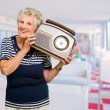 Happy Mature Woman Holding Radio - Stock Photo