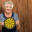 Happy Mature Woman Holding Dart Board — Stock Photo