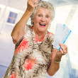 Senior Woman Holding Boarding Pass And Miniature - Stock Photo