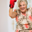 Happy Mature Woman Wearing Boxing Glove — Stock Photo #19527893