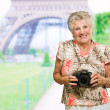 Happy Mature Woman Holding Camera - Stock Photo
