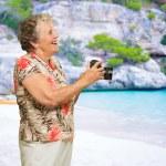 Senior Woman Holding Camera — Stock Photo #19527975
