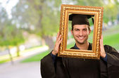 Graduate man looking through a frame — Stockfoto
