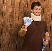 Niepełnosprawny mężczyzna z szyi klamra trzyma euro uwaga — Zdjęcie stockowe
