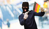 Man wearing a robber mask and holding airplane miniature and fla — Foto de Stock