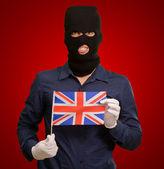 Porträtt av en man som bär mask hålla en flagga — Stockfoto
