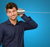 若い男がブリキ缶の電話から聞く — ストック写真