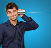 Young Man Listening From Tin Can Telephone — Stock Photo