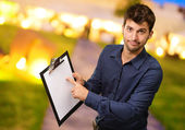 Young Man Pointing On Clipboard — Stock fotografie