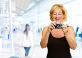 Happy Mature Woman Holding Camera — Stock Photo