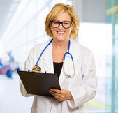 Mature Doctor Holding Clipboard — Photo