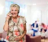 Ritratto di donna senior allegra con cuffia telefonica — Foto Stock