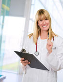 Happy female doctor holding a clipboard — Stock Photo