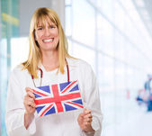 Happy Doctor Holding British Flag — Stock Photo