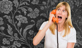 Shocked woman talking on telephone — Stock Photo
