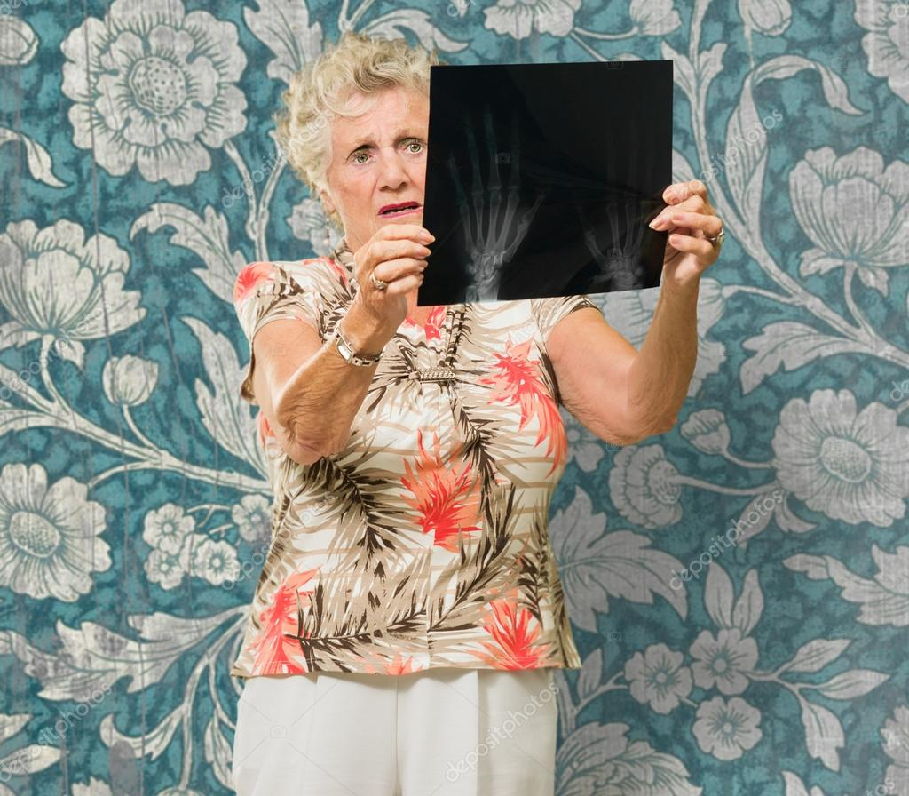 Senior Woman Holding X Ray Report On Wallpaper  Stock Photo #19528103