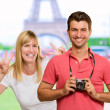 Happy Young Man Holding Camera In Front Of Woman Gesturing — Stock Photo #19536403