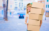 Woman holding a pile of boxes — Stock Photo