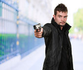 Handsome man pointing with gun — Stock Photo