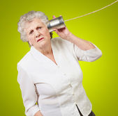 Portrait of a senior woman hearing with metal tin — Stock Photo