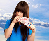 Girl looking through empty popcorn packet — Stock Photo