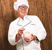 Chef Putting Coin In Piggybank, Indoor — Stock Photo