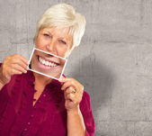 Senior Woman With Manifying Glass Showing Teeth — Stock Photo