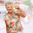 Mature Woman Holding Juice Glass — Stock Photo #19550021